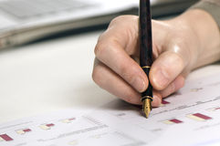 Hand with pen and graphics. Close up of a hand holding a pen above some papers with graphics. Laptop on the background Royalty Free Stock Image