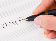 Hand with pen and music sheet Stock Photography