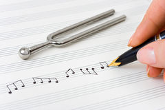 Hand with pen and music sheet. Musical background Stock Image