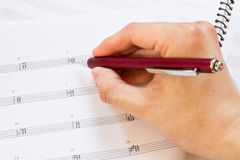 Hand with pen and music sheet Royalty Free Stock Image