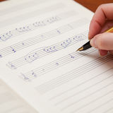 Hand with pen and music sheet Stock Images