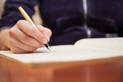 Hand with pen and music sheet Stock Image