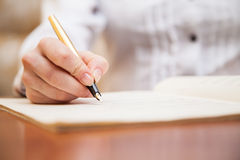 Hand with pen and music sheet. Hand pointing with pen to music book with handwritten notes Royalty Free Stock Photo