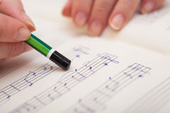 Hand with pen and music sheet. Hand pointing with pen to music book with handwritten notes Stock Photos