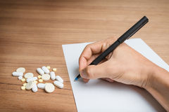 Hand with pen over blank paper form with pills Royalty Free Stock Photos