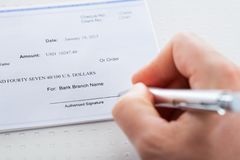 Hand with pen over checkbook Royalty Free Stock Photo