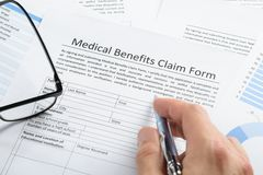 Hand with pen over medical claim application Stock Photos