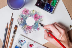 Hand with pen painting. With watercolor abstract floral with white circle in the center Stock Photos