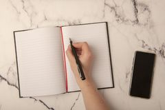 Hand with pen on paper. With copy space stock image