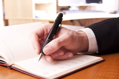 Hand pen paper table fingers Royalty Free Stock Images