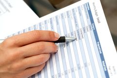 Hand with pen pointing on financial document. Royalty Free Stock Images