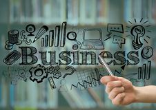 Hand with pen pointing to black business doodles against blurry bookshelf and teal overlay Royalty Free Stock Image