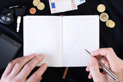 Hand with pen ready to write on a notepad Stock Photo