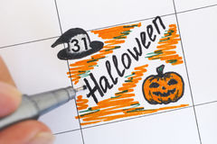 Hand with pen and reminder Halloween in calendar Royalty Free Stock Photos