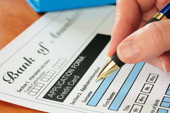 Hand with Pen Signing Credit Card Form Stock Images