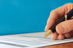 Hand with Pen Signing Form Closeup Blue Background Royalty Free Stock Images