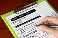 Hand with Pen Signing Form on Green Clipboard Royalty Free Stock Photography