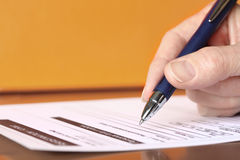 Hand with Pen Signing Form on Orange Background Royalty Free Stock Photos