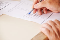 Hand with pen solving crossword puzzle Royalty Free Stock Images