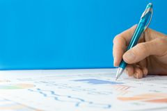 Hand with Pen working on Graphs Royalty Free Stock Photos