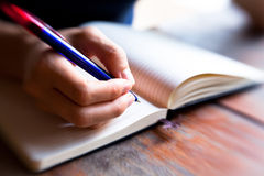 Hand pen writes in a notebook Royalty Free Stock Images