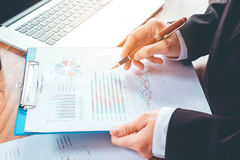 Hand with a pen writing on the business paper. Report chart Stock Image
