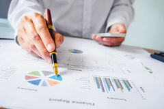 Hand with a pen writing on the business paper. Report chart Stock Photos