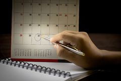 Hand with pen writing on calender. For note or make and plan hand holding pen and point at date on calender royalty free stock photo
