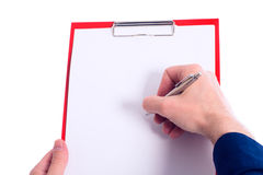 Hand with pen is writing at a clipboard Royalty Free Stock Images