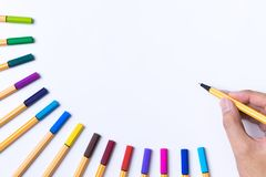 Hand with pen writing down on copy space colorful pens Royalty Free Stock Images
