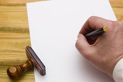 Hand with pen writing on empty paper Stock Image