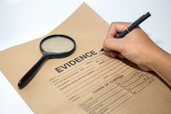 Hand with pen writing on evidence paper with magnifying glass. Hand with pen writing on blank evidence paper bag with magnifying glass stock photography