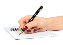 Hand with pen writing on notebook Stock Image