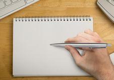 Hand with pen writing in notepad Stock Image