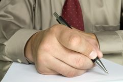 Hand with pen writing on the page Stock Images