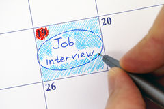 Hand with pen writing reminder Job Interview in calendar Royalty Free Stock Image