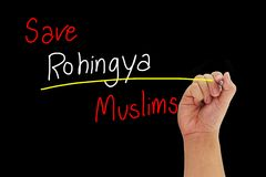 Hand with pen writing Save Rohingya Muslims from human trafficking isolated on black background Stock Images