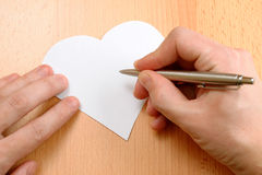 Hand with pen writing on Valentine's Day card Stock Photography