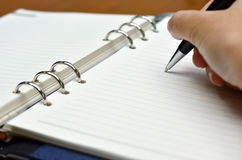 Hand with a pen writing on white paper Royalty Free Stock Image