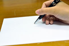 Hand with a pen writing on white paper Royalty Free Stock Images