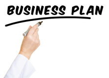 Hand with pen writing Business Plan Stock Photo