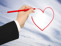 Hand with pencil draws the heart Royalty Free Stock Images