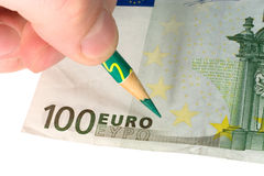 Hand with a pencil and a euro bill Stock Photography