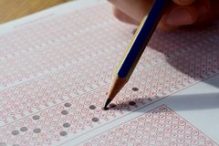Hand with pencil filling out answers on exam test answer sheet. Men hand with pencil filling out answers on exam test answer sheet stock photo