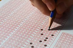 Hand with pencil filling out answers on exam test answer sheet. Men hand with pencil filling out answers on exam test answer sheet stock photography