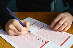 Hand with pencil filling out answers on exam test answer sheet. Men hand with pencil filling out answers on exam test answer sheet royalty free stock photography