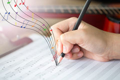 Hand with pencil and music sheet. Woman hand with pencil and music sheet Stock Image