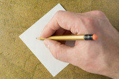 Hand with pencil and piece of sheet. Hand with a pencil and a piece of white paper Stock Image