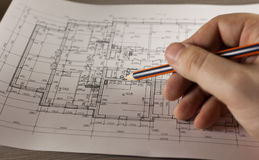 Hand with pencil on plan of the house stock photos