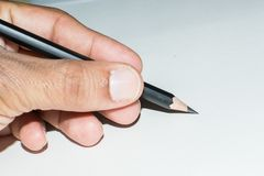 Hand with Pencil in writing gesture. Or writing position on white paper royalty free stock photos